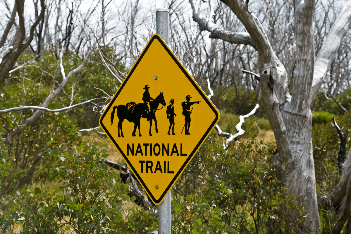 Yellow National Trail sign depicting people walking with horses