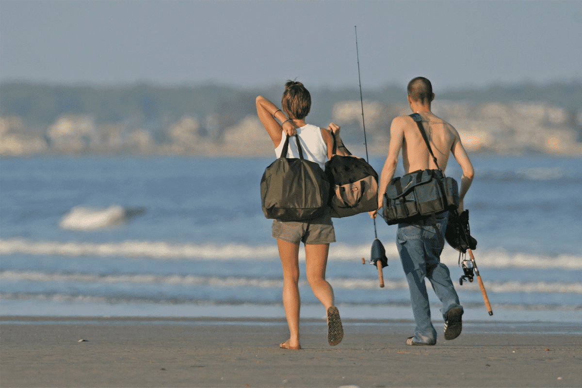 Male and female walking down the beach with go bags and fishing rods