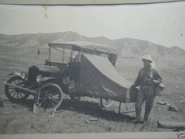 Fisherman stands next to a 1915 L.F. Shilling Auto Camp vehicle, an early part of RV History.