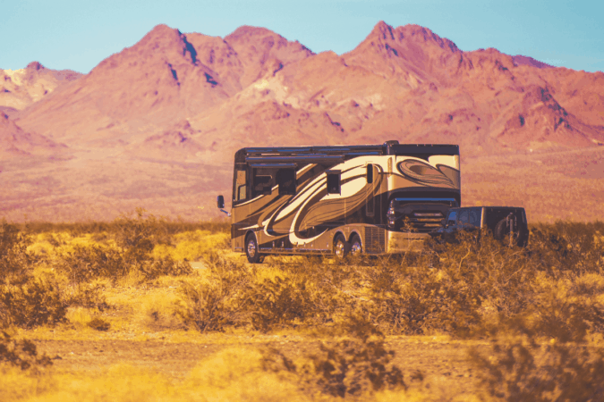 Class A motorhome towing a Jeep in a red desert