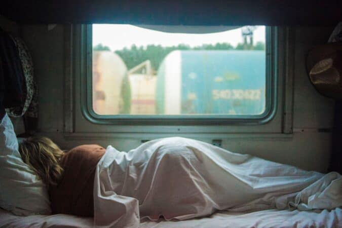 Woman lying on RV mattress with a big window in the background