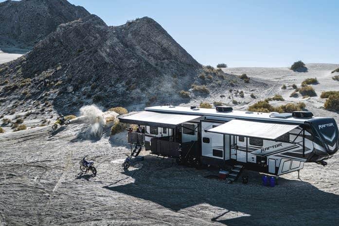 Raptor fifth wheel RV parked in desert terrain with people dirt biking