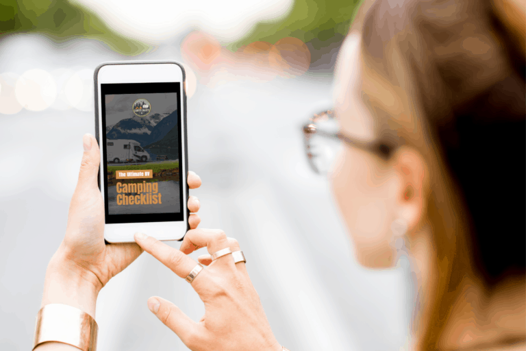"""woman holding a phone and the screen says """"The Ultimate RVing Camping Checklist"""""""