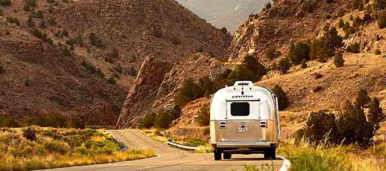 Airstream RV being driven down a winding road