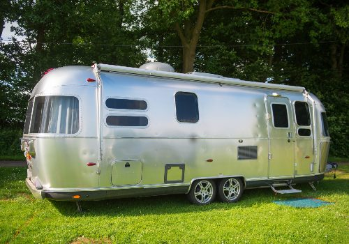 Airstream trailer parked under the tree