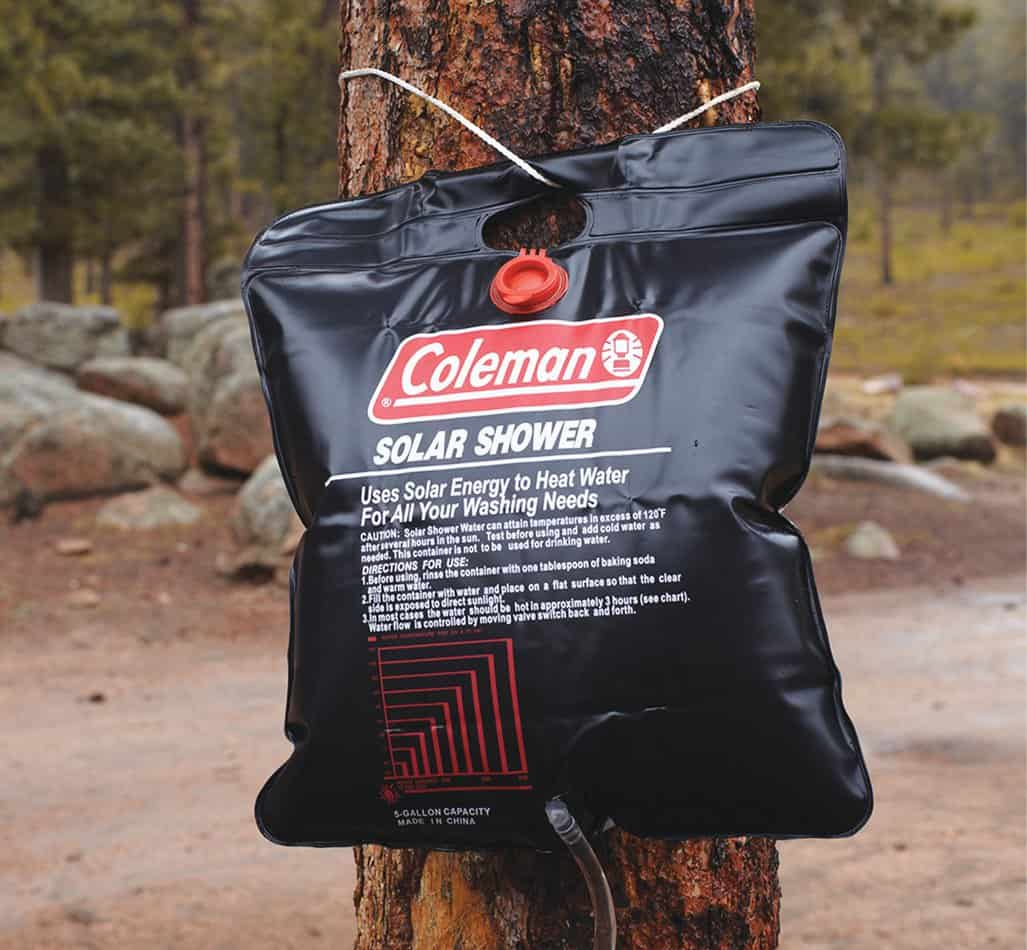 Black solar shower bag attached to a tree.