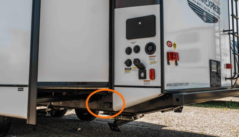 Back end of a travel trailer with hidden GPS tracker circled in orange.