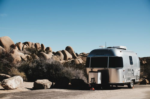 Gray travel trailer parked beside brown rocks