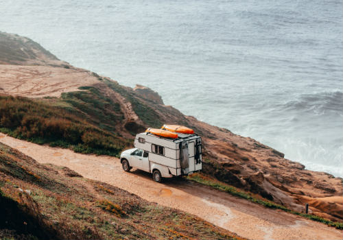 Man and woman sitting on blue rv near mountain during daytime