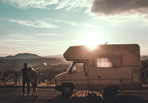 Man and woman are standing beside camper on the street