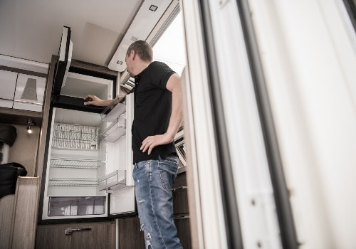 Man is checking the RV refrigerator