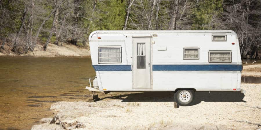 An old RV parked near a river