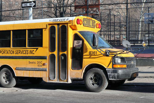 School bus register as rv parked near the basketball court