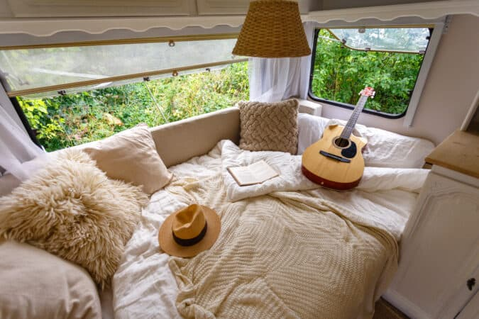 Bed in RV with guitar, hat, and pillows.