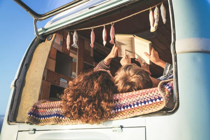 mom and son reading a book in the back of a vintage campervan