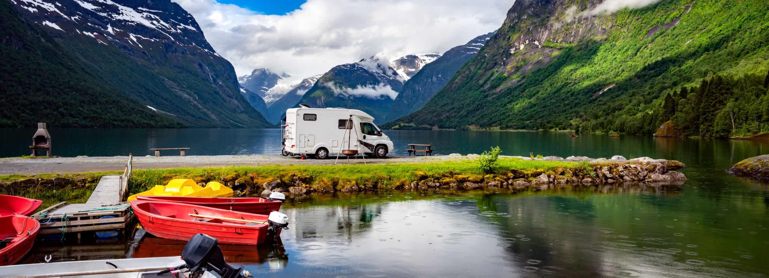 Motorhome parked by a lake surrounded by mountains