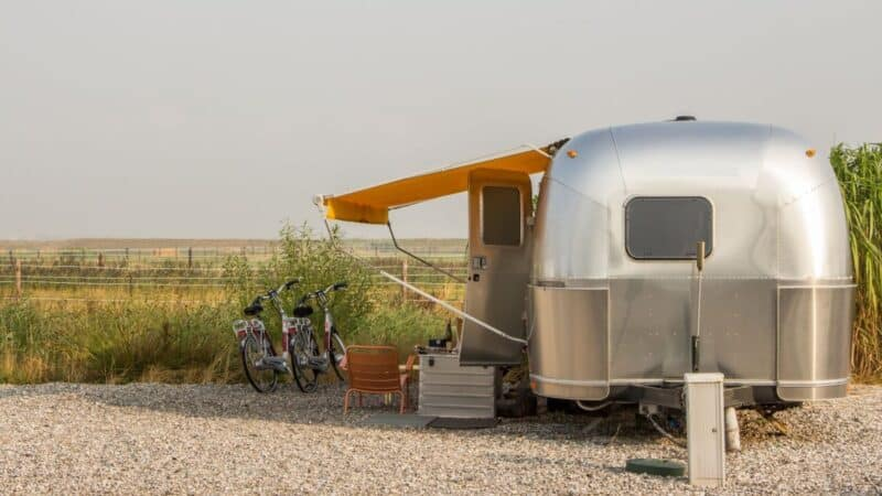 Airstream with awning extended parked in a yard