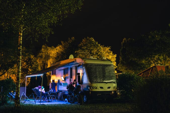 People sit under an awning and watch TV on RV entertainment center