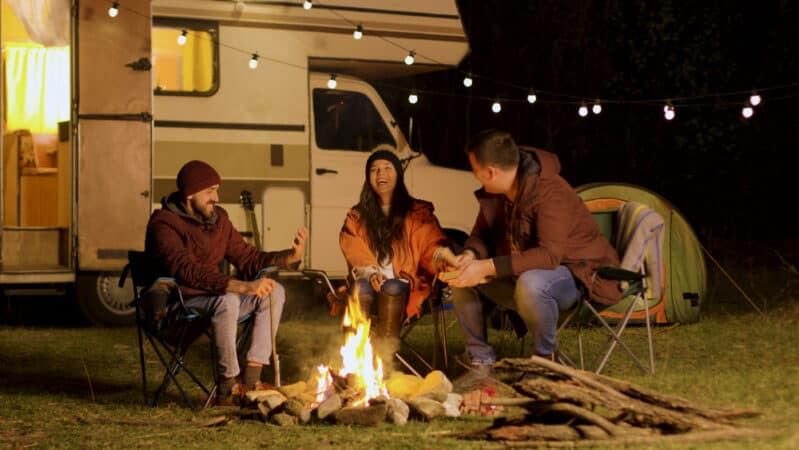 A group of RVers enjoy a campfire outside a well lit RV.