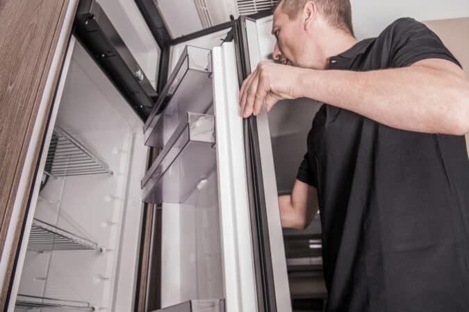 Man opening an RV fridge door