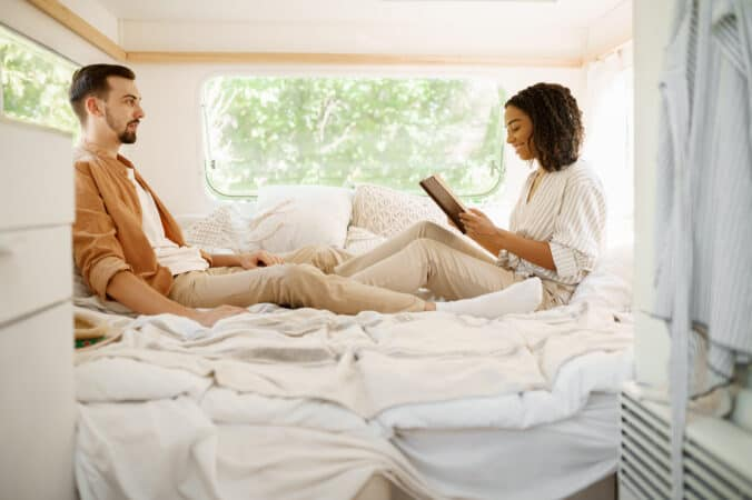 A couple sits in bed in their RV master bedroom