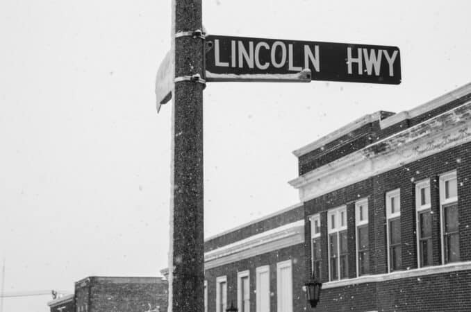 A black and white photograph of the Lincoln Highway sign