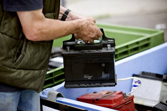 A senior man recycling an AGM battery