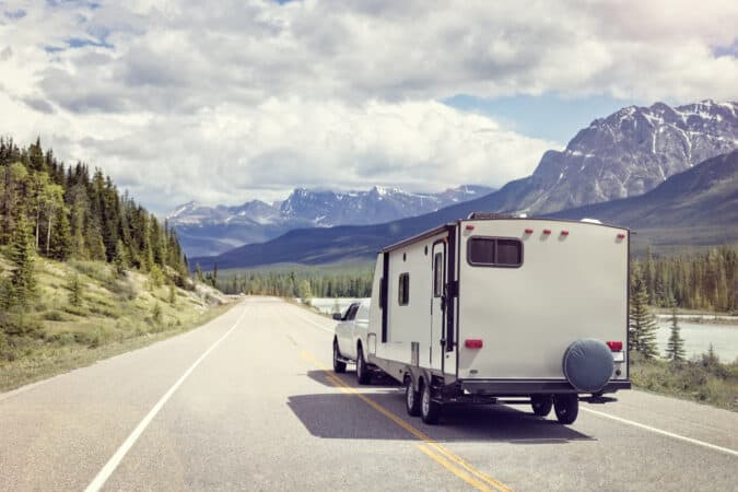 A truck and RV travel down a scenic highway with stream and mountian