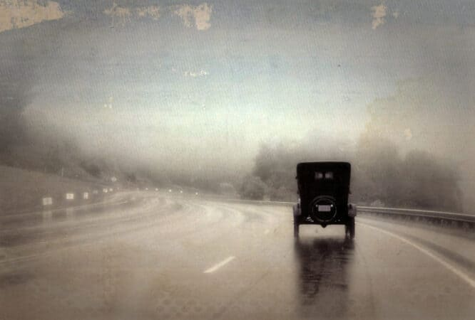 Model A Ford cruises down a blacktop highway on Route 66