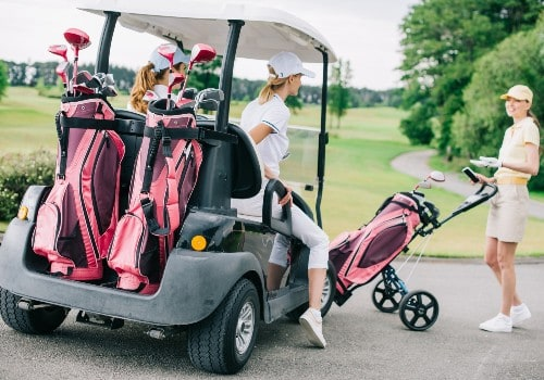 Smiling female golf players at the golf cart