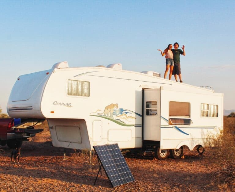A couple standing on top of their fifth wheel RV