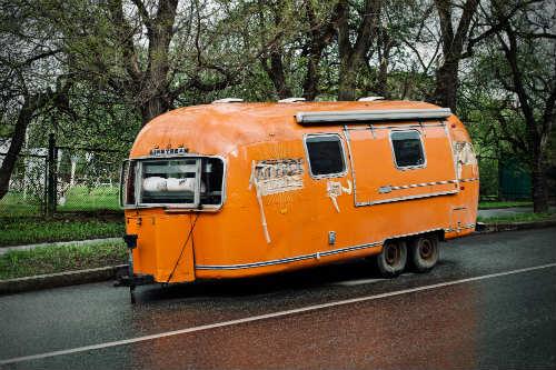 Travel trailer on road beside trees