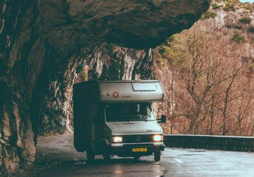 White truck camper on road under rock formation